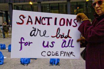 CodePink activist protests U.S. worldwide sanctions. [Source: globalresearch.ca]