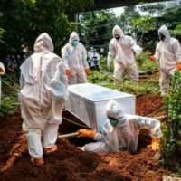 Health workers bury a suspected victim of COVID-19 in Jakarta, Indonesia
