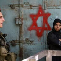AN ISRAELI SOLDIER KEEPS GUARD NEAR A PALESTINIAN WOMAN STANDING NEXT TO STAR OF DAVID GRAFFITI SPRAYED BY ISRAELI SETTLERS AT AN ARMY CHECKPOINT IN THE CENTER OF HEBRON, MAY 18, 2009. (PHOTO: MENAHEM KAHANA/AFP/GETTY IMAGES)