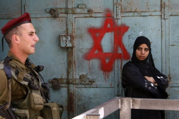 | AN ISRAELI SOLDIER KEEPS GUARD NEAR A PALESTINIAN WOMAN STANDING NEXT TO STAR OF DAVID GRAFFITI SPRAYED BY ISRAELI SETTLERS AT AN ARMY CHECKPOINT IN THE CENTER OF HEBRON MAY 18 2009 PHOTO MENAHEM KAHANAAFPGETTY IMAGES | MR Online