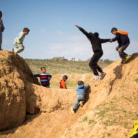 Israeli Arab Bedouin children play before a rally marking the 40th anniversary of Land Day and against a plan to uproot the village of Umm Al-Hiran, in Umm Al-Hiran, the Negev desert, southern Israel, Wednesday, March 30, 2016. Land Day commemorates the killing of six Arab citizens of Israel by the Israeli army and police on March 30, 1976 during protests over Israeli confiscations of Arab land. (AP Photo/Ariel Schalit)
