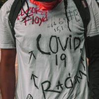 Man in shirt with covid-19 George Floyd racism writing