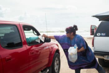   MARY HELEN FLORES A MEMBER OF BOCA CHICA BOUND AN ORGANIZATION THAT PLANS BEACH CLEANUPS HANDS TRASH BAGS TO VISITORS DURING A SATURDAY CLEANUP   MR Online