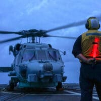 U.S. seaman on a guided-missile destroyer directs a helicopter during operations in the South China Sea in 2020. (U.S. Navy, Andrew Langholf)
