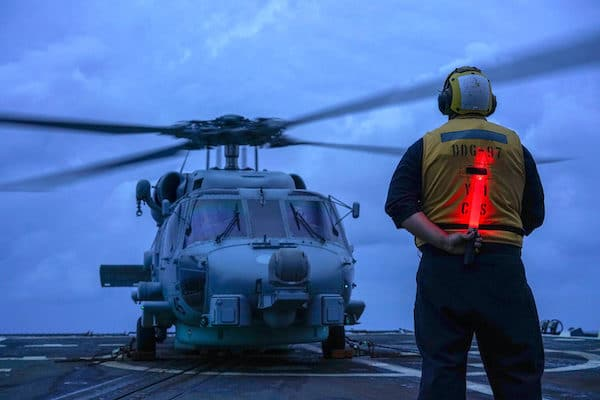 MR Online | US seaman on a guidedmissile destroyer directs a helicopter during operations in the South China Sea in 2020 US Navy Andrew Langholf | MR Online