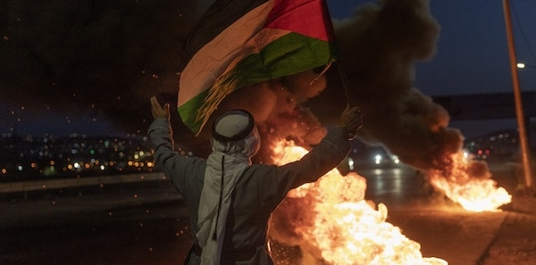 | A protester flies a Palestinian flag at Israeli troops during a demonstration in support of Palestinian prisoners in Israeli jails at the entrance of the occupied West Bank city of Nablus Monday September 13 2021 | MR Online