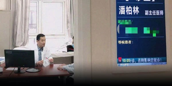  Pan Bolin talks with a man at his clinic in Beijing   MR Online