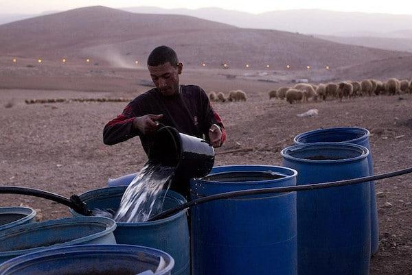 | A Palestinian farmer fills water tanks in the West Bank village of Khirbet alMakhoul Jordan Valley October 9 2013 Activestillsorg | MR Online